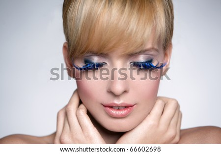 Portrait of a beautiful woman with beautiful makeup isolated on grey - stock photo