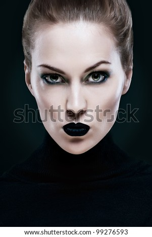 Portrait of a beautiful woman, with black lips. On a black background - stock photo