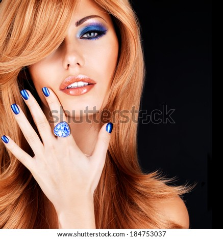 portrait of a beautiful woman with blue nails, blue makeup and  long red hairs  on black background - stock photo