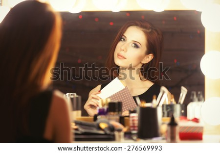 Portrait of a beautiful woman with certificate near a makeup artist mirror. Photo in retro color style. - stock photo