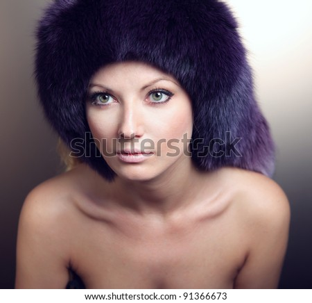 portrait of a beautiful woman with fur on the head - stock photo