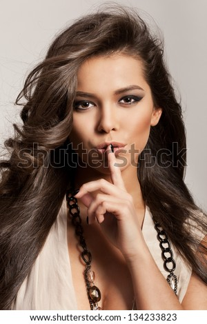 Portrait of a beautiful woman with healthy long brown hair and fresh makeup making a hush gesture. Wavy Hair. Hairstyle. Not isolated on grey background. Indoor - stock photo