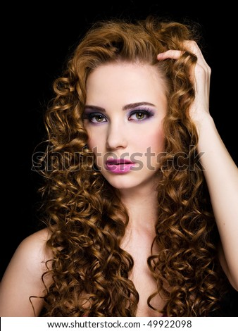 Portrait of a beautiful  woman with  long curly hairs - On a black background - stock photo