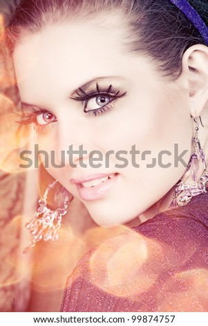 portrait of a beautiful woman with long false feather eyelashes and bright make-up on golden lights background - stock photo