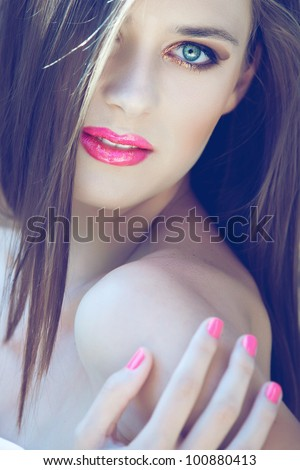 portrait of a beautiful woman with long hair and bright pink lips wearing glitter gold eyeshadow - stock photo