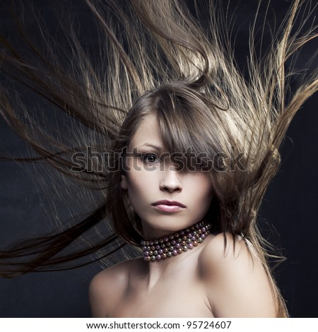 Portrait of a beautiful woman with long straight hair developing on a black background - stock photo