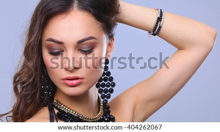 Portrait of a beautiful woman with necklace, isolated on gray background - stock photo