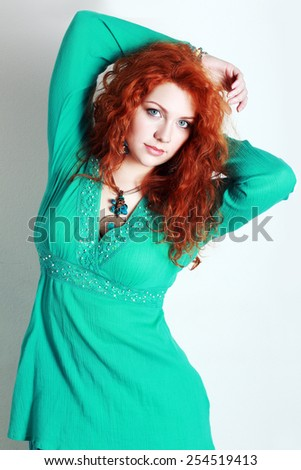 portrait of a beautiful woman with red curly hair. wearing a romantic green or turquoise dress  - stock photo