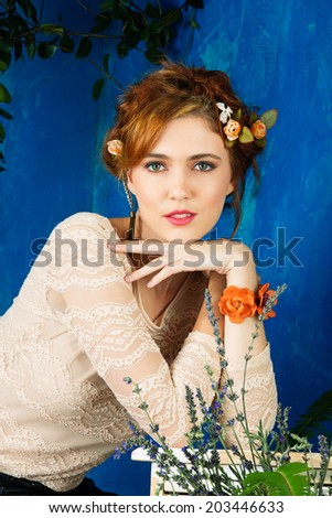 portrait of a beautiful woman with red hair in braided hairstyle and flowers in her hair. wearing leather orange bracelet grunge painted background - stock photo