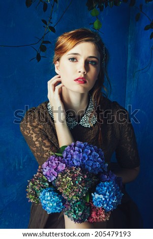 portrait of a beautiful woman with red hair in curly braided hairstyle. wearing a romantic lace dress and holding flowers on grunge painted background  - stock photo