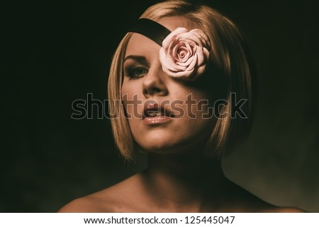 Portrait of a beautiful woman with rosebud on fillet - stock photo