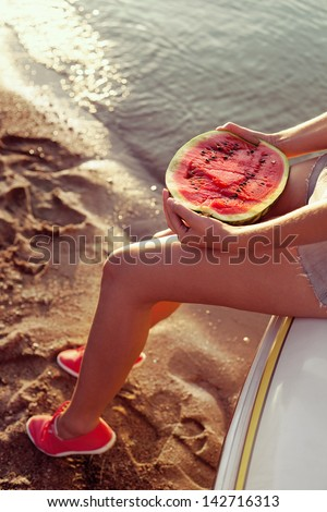 Portrait of a beautiful woman with watermelon on the beach. Lifestyle - stock photo