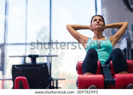 Portrait of a beautiful woman workout on exercises machine in fitness gym - stock photo