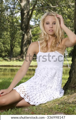 Portrait of a beautiful young adult attractive pretty blond sensuality woman in the garden - stock photo