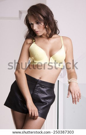 portrait of a beautiful young adult sensuality attractive and sexy pretty brunette woman in yellow lingerie bra and black skirt in luxury style exclusive hotel apartment - stock photo