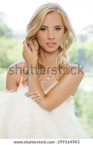 Portrait of a beautiful young adult sensuality attractive and sexy smiling pretty happy blonde woman in white fur on morning sunlight window - stock photo