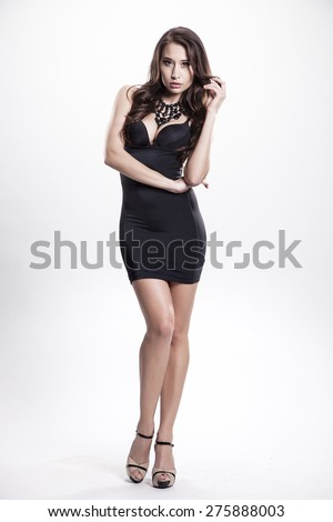 Portrait of a beautiful young adult slim sexy and attractive sensuality pretty brunette woman in black elegance fashionable dress isolated on white background - stock photo