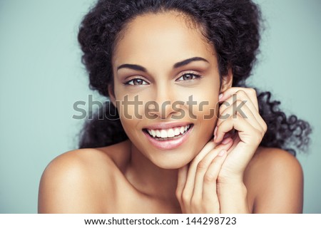 Portrait of a beautiful young African woman smiling. - stock photo