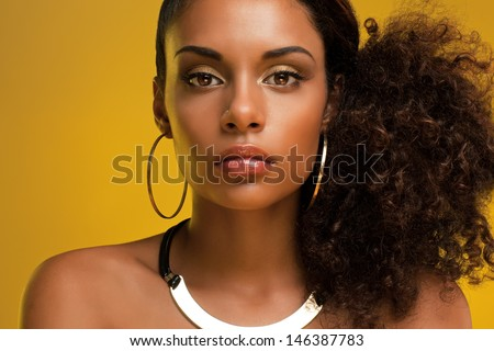Portrait of a beautiful young African woman wearing gold jewelry. - stock photo