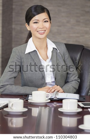 Portrait of a beautiful young Asian Chinese woman or businesswoman in smart business suit sat in an office or boardroom - stock photo