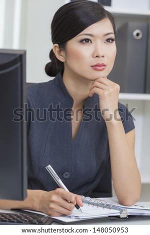 Portrait of a beautiful young Asian Chinese woman or businesswoman sitting at a desk in office writing in her personal organizer. - stock photo