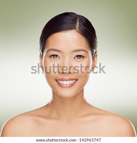 Portrait of a beautiful young Asian woman smiling. - stock photo