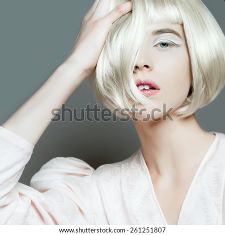 Portrait of a beautiful young blond woman with short hair in studio on gray background - stock photo