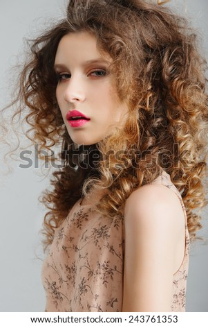 Portrait of a beautiful young blonde girl in the studio with curly hair - stock photo