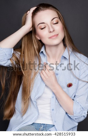 Portrait of a beautiful young blonde girl. She is wearing a denim shirt and a white T-shirt. She has gorgeous shiny hair and clear skin. Her eyes are closed, she smiles. - stock photo
