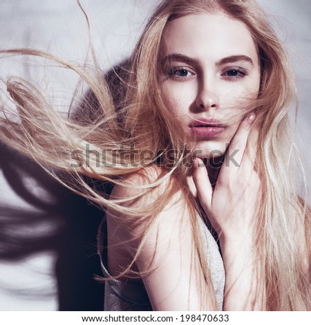 Portrait of a beautiful young blonde girl with developing hair - stock photo