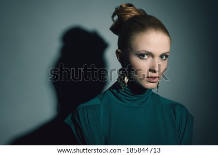 Portrait of a beautiful young blonde wearing green (blue) dress and ethnic earrings. Model posing over light-blue background. Perfect skin and stylish hairdo. Deep shadows. Copy-space. Studio shot - stock photo
