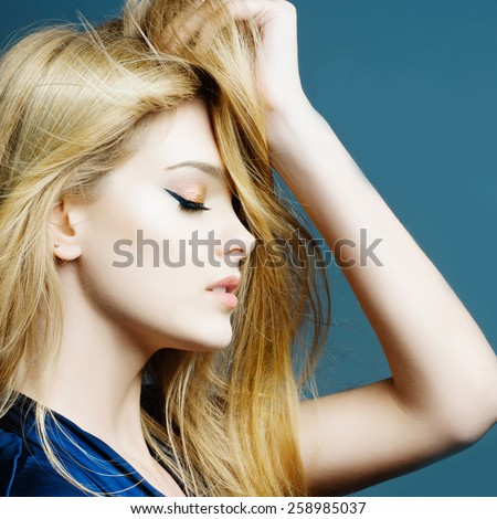 Portrait of a beautiful young blonde woman in studio on a blue background holding a hand through his hair, beauty concept - stock photo