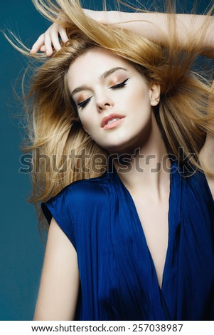 Portrait of a beautiful young blonde woman with long hair in a studio on a blue background, the concept of beauty - stock photo