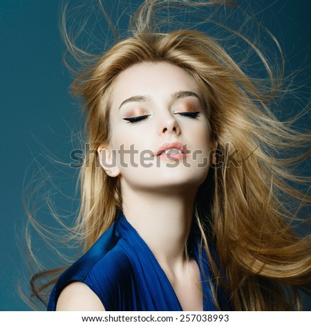 Portrait of a beautiful young blonde woman with long hair in a studio on a blue background, the concept of health and beauty - stock photo