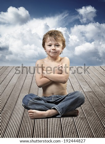 Portrait of a beautiful young boy sitting in yoga pose on a wooden floor against cloudy blue sky - stock photo