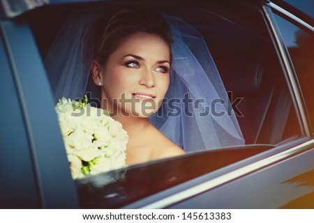 Portrait of a beautiful young bride in the car  - stock photo