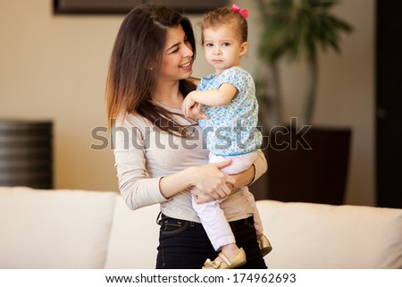 Portrait of a beautiful young brunette carrying her cute little daughter in the living room - stock photo
