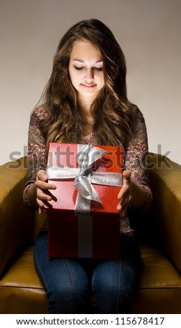 Portrait of a beautiful young brunette peeking inside shiny red gift box in creative lighting. - stock photo