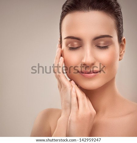Portrait of a beautiful young brunette posing with her eyes closed. - stock photo