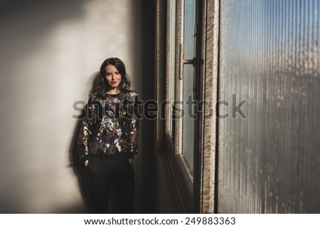 Portrait of a beautiful young brunette with long hair posing beside a window - stock photo