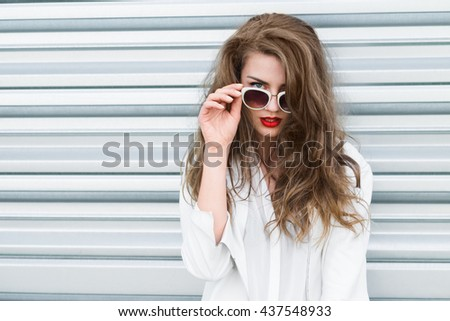 portrait of a beautiful young brunette with stylish sunglasses on a sunny day close-up - stock photo