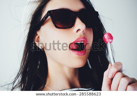 Portrait of a beautiful young brunette woman in a hat with candy in studio, lifestyle - stock photo