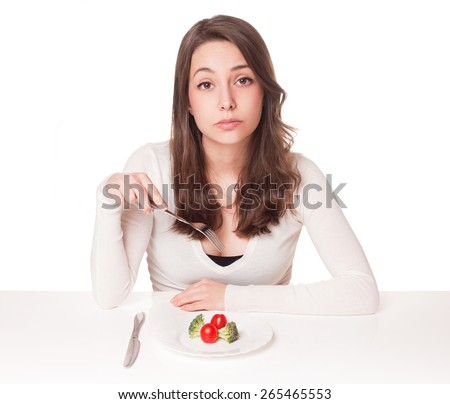 Portrait of a beautiful young brunette woman in diet dilemma. - stock photo