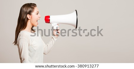 Portrait of a beautiful young brunette woman using loudspeaker. - stock photo