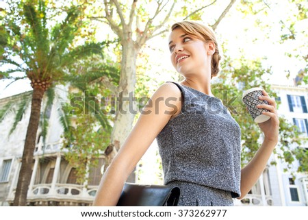 Portrait of a beautiful young business woman commuter walking passing classic buildings in city, holding a coffee paper cup, turning back. Professional drinking coffee, on the go lifestyle exterior. - stock photo