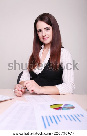 Portrait of a beautiful young business woman doing some paperwork in office  - stock photo