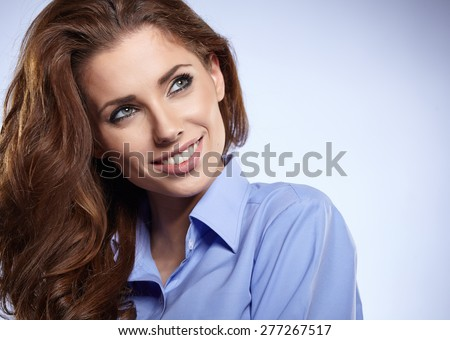 Portrait of a beautiful young business woman standing against blue background  - stock photo