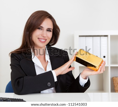 Portrait of a beautiful young businesswoman holding gold bar at office desk - stock photo