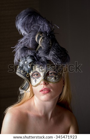 portrait of a beautiful young caucasian woman in a black venetian mask on a dark grey background - stock photo
