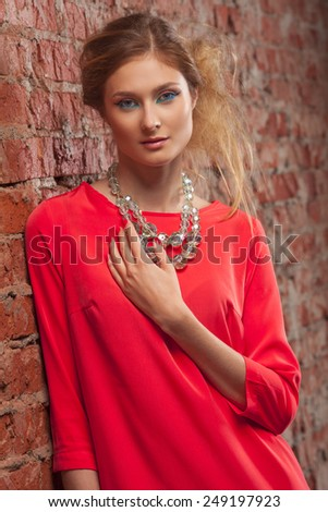 Portrait of a beautiful young caucasian woman in red dress - stock photo